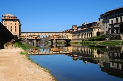 A Beautiful view of the famous Old Bridge Ponte Vecchio and Uffizi Gallery with blue sky in Florence as seen from Arno Royalty Free Stock Photos