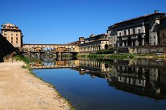 A Beautiful view of the famous Old Bridge Ponte Vecchio and Uffizi Gallery with blue sky in Florence as seen from Arno river Royalty Free Stock Image