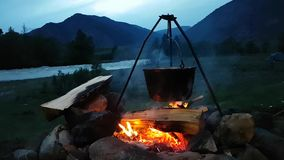 Beautiful view of the fire and the pot basking on the fire. Romantic evening in nature: warm flame, river, tent in the distance.