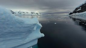 Beautiful view of the floating ice in the bay. Andreev. Beautiful view of the floating ice in the bay. Beautiful scenery of rocks under the snow and iceberg stock footage