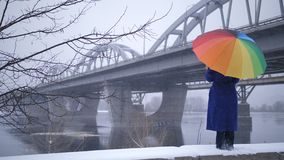 Woman with rainbow umbrella near bridge in winter. Beautiful view of full length woman standing near city bridge under rainbow umbrella during wind and snowfall stock footage