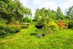Beautiful view on garden with grill, table, chair Stock Photography