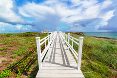 Beautiful view of a gazebo path leading toward the beach and ocean against magic blue sky background on Cuban Cayo Guillermo Isla. Amazing gorgeous beautiful Royalty Free Stock Photos