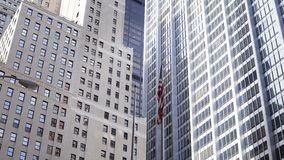 Beautiful view of the glass skyscrapers in New York, USA. National American flag waving on the wind. Financial district with offices stock video footage