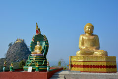 Beautiful view of the golden Buddha statue with Mount Popa, Myanmar. Beautiful view of the golden Buddha statue with Mount Popa on the background. Situated in Stock Images