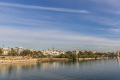 Beautiful view of the Guadalquivir river and a part of the city of Seville Spain. On a wonderful sunny day and a blue sky with few white clouds royalty free stock image