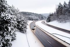 Beautiful view of a highway on winter day. Cars driving through pine forest covered with snow. Beautiful view of a highway on chilly winter day. Cars driving stock photography