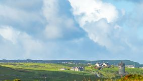 Beautiful view of a hill with houses and castle Doonagore in the village of Doolin stock image
