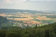 Typical german landscape with a village, hills, forest and wind turbines in the background stock image