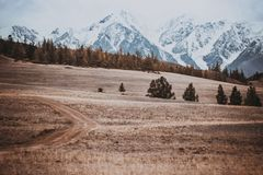 Beautiful view of the hills with a dirt road. To the snowy peaks. Colorful mountain valley with rocks stock image