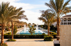 Beautiful view from the hotel swimming pool with palm trees. Beautiful view of the hotel in tropical luxury with swimming pool with palm trees on the shore of Royalty Free Stock Photo