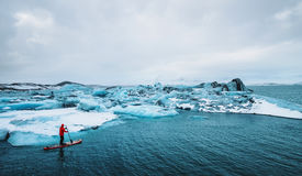 Beautiful view of icebergs glacier lagoon with a guy paddle boarding sup. Global warming and climate change concept royalty free stock photography