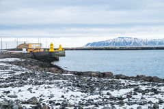 Beautiful view of Iceland winter season and Yellow lighthouse to. Wer on stone breakwater rekjavik port with snow-capped mountain in the background Stock Photos
