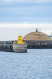Beautiful view of Iceland winter season and Yellow lighthouse to. Wer on stone breakwater rekjavik port with snow-capped mountain in the background Royalty Free Stock Photography