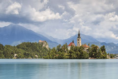 Beautiful view of Lake Bled with Island, Church And Castle With Mountain Range Stol, Vrtaca, Begunjscica In The Background- Bled Stock Images