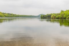 Beautiful view of a lake with many trees and a gray sky. And sharp reflection of it in the water in Maasmechelen Belgium, copy space, travel, adventure concept royalty free stock images