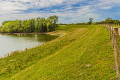 Beautiful view of a lake with trees and green grass royalty free stock photo