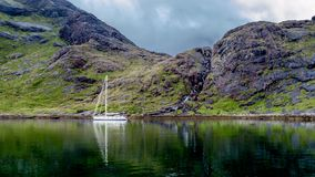 Beautiful view of the loch coruisk at the Isle of Skye with a waterfall in the background. And an anchored yacht in the loch, Scotland, United Kingdom stock images