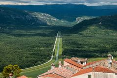 A beautiful view of the long road leading from the town with red tiled roofs far away to the horizon with green hills. A view of the long road leading from the Royalty Free Stock Images