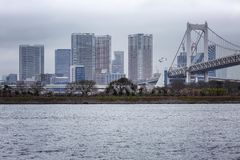 Beautiful view of the modern buildings and the bridge over the river. Gloomy sky Odaiba Island. Horizontal royalty free stock image