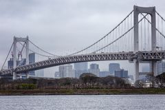 Beautiful view of the modern buildings and the bridge over the river. Gloomy sky Odaiba Island. Horizontal stock images