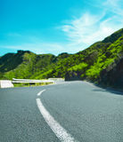 Beautiful view of mountain forest and blue sky. Turning mountain highway with blue sky and empty rural asphalt perspective with white line road Royalty Free Stock Image