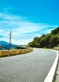 Beautiful view of mountain forest and blue sky. Turning mountain highway with blue sky and empty rural asphalt perspective with white line road Stock Photo