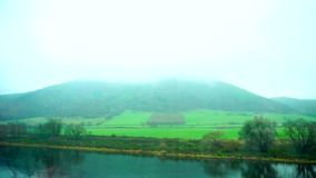 Beautiful view of  mountains in  fog,  river and green fields from  window of passing train in  autumn. Pretty green landscape opens from  train window at stock video footage