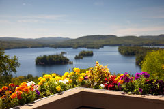 Beautiful view on the mountains lake from balcony with yellow an. Beautiful colorful view on the mountains lake from balcony with yellow and red flowers Royalty Free Stock Photos