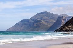 Beautiful view of mountains near Hout Bay, Cape Town, South Africa, seen from Noordhoek Long Beach. White sand beach and waves with spray. Noordhoek Beach is a Stock Photo
