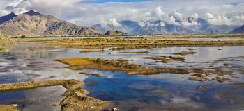 Beautiful view of natural plateau with swamp, stream and water reflection of the bright day sky background. Scenic Trip to Tibet stock photography