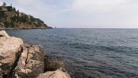 Beautiful view of nature. The sea with small waves, rocky cliff and the city in the distance stock video footage