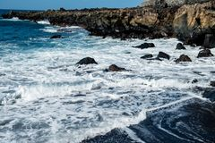 Beautiful view on ocean water and black lava sand royalty free stock image