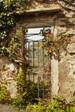 Beautiful view, through the old gate. Decorated with flowers in Italy Royalty Free Stock Image