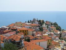 Beautiful view of the old Greek city with red tiled roofs temple and endless blue sea on a hot Sunny summer day royalty free stock image