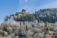 Beautiful view of a part of the Alhambra with a contrast between green trees and dry plants. On a wonderful sunny day in Granada Spain stock photography