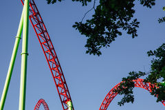 Beautiful view of the peak roller coaster track in Red and green against blue sky,. Around the green leaves of the park trees Royalty Free Stock Photos