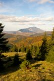 View of Postavaru mountain ridge in autumn season. Beautiful view of Postavaru mountain ridge in autumn season, with colorful forest and blue sky Royalty Free Stock Images
