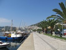 Beautiful view of the promenade of Kavala, where tourists and townspeople walk, surrounded by palm trees and parked pleasure boats royalty free stock images