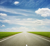 Beautiful view of roadway. Green field and blue sky Stock Images