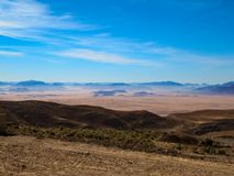 Beautiful view of the rocky brown and blue mountains against the bright blue sky stock images