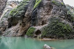 Beautiful view of a rocky slope with green moss and the Guadalevín river with its turquoise waters. Wonderful day in the city of Ronda in the province of royalty free stock images