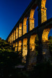Beautiful view  of roman Aqueduct Pont del Diable in Tarragona at sunset with people jogging in front of it Royalty Free Stock Photo