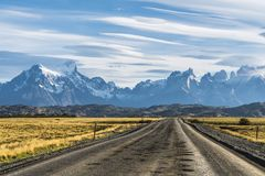 Beautiful view of rural road with golden yellow grass with background of nature cuernos mountains peak with cloud in autumn,. Torres del Paine national park stock photo