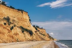 Beautiful view of sandy cliff near sea beach. Landscape of beach cliff and waves in sunny weather. Summer vacation concept. Exploring interesting places stock images