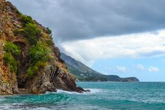 Beautiful view of the sea. The mountains descend into the sea. The sky with rain clouds, the waves foam. Adriatic Sea. Montenegro.  stock images