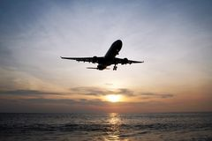 The beautiful view on a sea with plane in a sky during a colorful sunset. Stock Photos