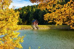 Beautiful view of small wooden house on bank of lake near forest during autumn royalty free stock photography