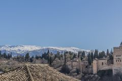 Beautiful view of snowy mountains, trees on a hill, a tile roof and a small part of the Alhambra stock photo