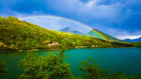 A beautiful view of the spring landscapes and a rainbow over the lake. Dark clouds in the background. royalty free stock photos